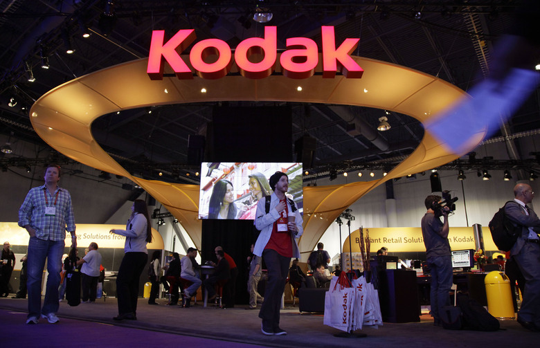 FILE – In this Jan. 11, 2012 file photo, buyers and industry affiliates pass by the Kodak exhibit at the 2012 International CES trade show in Las Vegas.  An independent legal review has determined that there were several flaws in how Eastman Kodak gave stock option grants to its CEO prior to the once formidable photography company being awarded a loan from the Trump administration.  (AP Photo/Julie Jacobson, File)