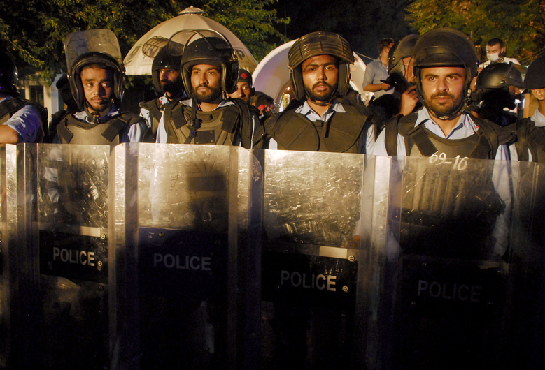 Police officers stand guard near Indian High Commission, while members of the Pakistani Hindu community stage a join a sit-in protest in Islamabad, Pakistan, Thursday, Sept. 24, 2020. Pakistan's minority Hindus rallied late on Thursday in Islamabad to protest the deaths of 11 members of a Hindu migrant family who died in India last month under mysterious circumstances. The protesters accuse India's secret service of poisoning the victims, who were found dead at a farmhouse in India's Jodhpur district in Rajasthan state. (AP Photo/A.M. Chaudary)