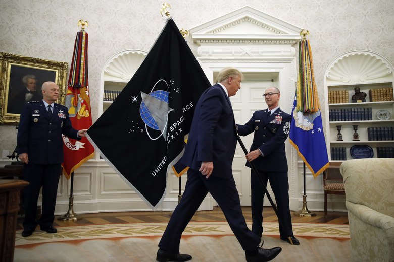 FILE – In this May 15, 2020 file photo, Chief of Space Operations at United States Space Force Gen. John Raymond, left, and Chief Master Sgt. Roger Towberman, right, hold the U.S. Space Force flagas President Donald Trump walks past it, in the Oval Office of the White House in Washington. On Sept. 1, 2020, Space Force, the first new U.S. military service since the creation of the Air Force in 1947 swore in some 20 members stationed at the Al-Udeid Air Base, Qatar in its first foreign deployment. (AP Photo/Alex Brandon, File)