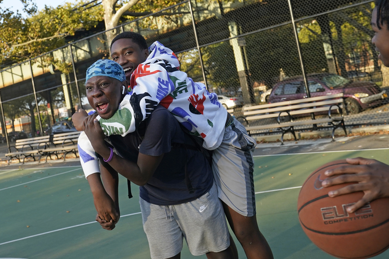 Kassan Perry, right, clowns around with a friend from the Marlboro Houses as he plays a game of pickup basketball, Monday, Sept. 28, 2020, in the Gravesend neighborhood of the Brooklyn borough of New York. The area has seen has seen a recent uptick rise in COVID-19 cases. New York Gov. Andrew Cuomo raised alarm Monday about the emergence of a handful of coronavirus hot spots in New York, saying just 10 ZIP codes represented more than a quarter of the state's new infections in recent testing. (AP Photo/Kathy Willens)