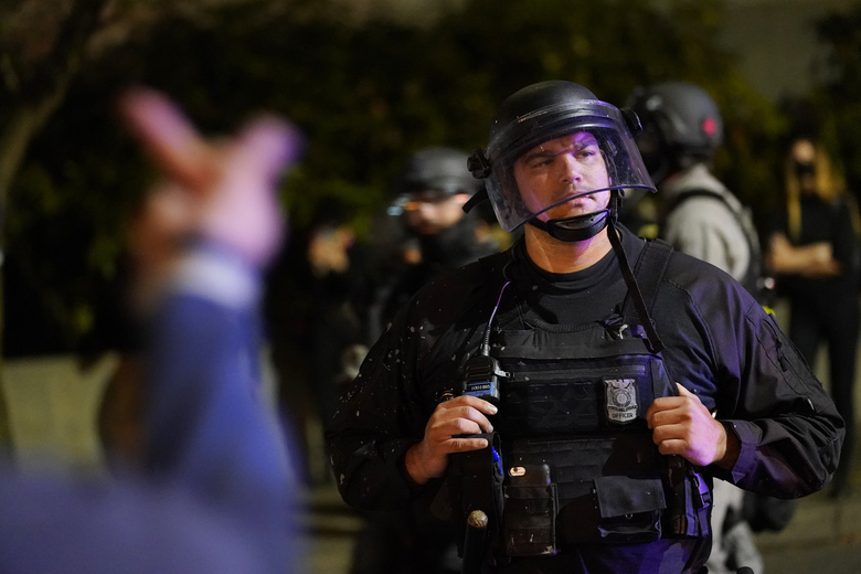 A protestor reacts toward a Portland police officer during protests Saturday, Sept. 26, 2020, in Portland. The protests which began since the police killing of George Floyd in late May often result in frequent clashes between protesters and law enforcement. (AP Photo/John Locher)