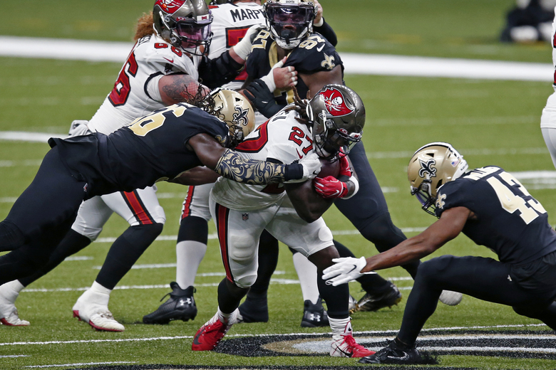 Tampa Bay Buccaneers running back Ronald Jones (27) carries against New Orleans Saints free safety Marcus Williams (43) and outside linebacker Demario Davis in the first half of an NFL football game in New Orleans, Sunday, Sept. 13, 2020. (AP Photo/Butch Dill)