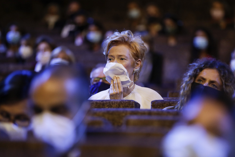 Actress Tilda Swinton sits in the auditorium wearing a mask during the opening ceremony of the 77th edition of the Venice Film Festival in Venice, Italy, Wednesday, Sept. 2, 2020. (AP Photo/Domenico Stinellis)