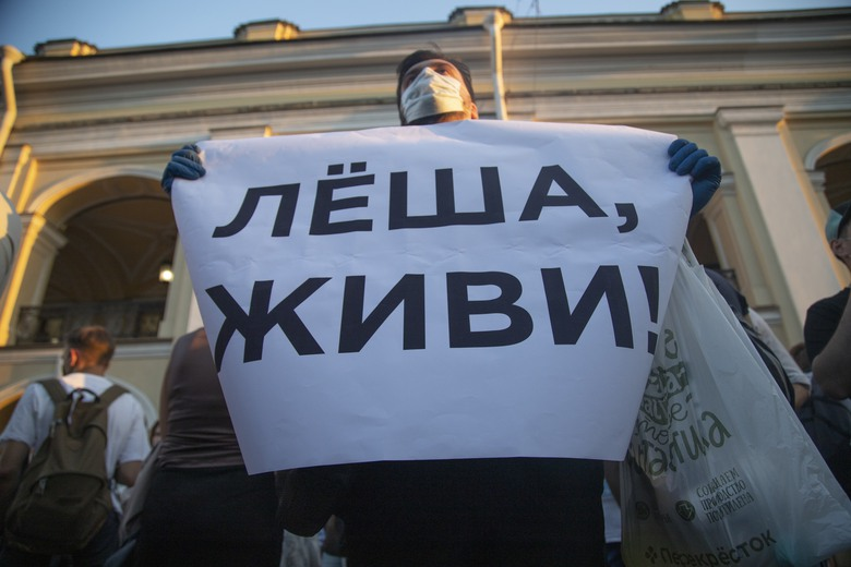 "FILE – In this Aug. 20, 2020, file photo, a protester holds a poster reading ""Lyosha, you must live!"" in support of Russian opposition leader and corruption fighter Alexei Navalny in the center of St. Petersburg, Russia. Navalny is in a coma in a Berlin hospital after suffering what German authorities say was a poisoning with a chemical nerve agent while traveling in Siberia on Aug. 20.  (AP Photo/Ivan Petrov, File)"