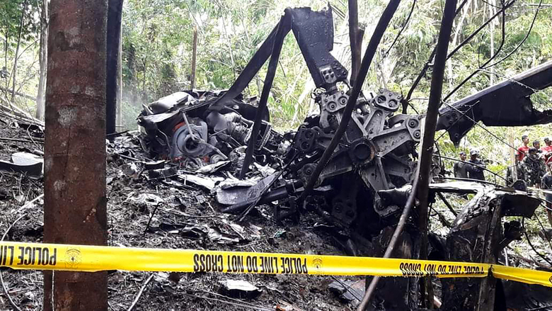 In this photo provided by the Lantawan Disaster Risk Reduction Management Office, rescuers check the remains of a Philippine air force S-76A Sikorsky helicopter after it crashed in Basilan island, southern Philippines on Wednesday Sept. 16, 2020. The helicopter was en route to airlift troops wounded from a recent suicide bombing crashed on a southern island Wednesday, killing all four crew members on board, officials said. (Lantawan Disaster Risk Reduction Management Office via AP)