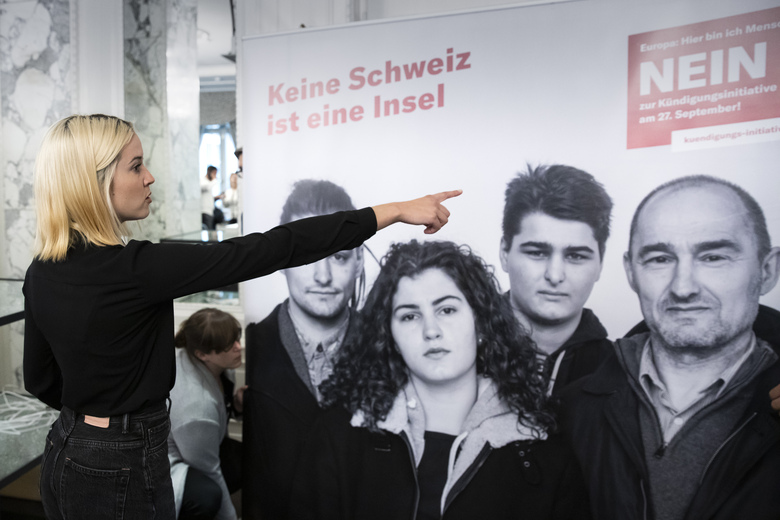 "Laura Zimmermann, Co-President of Operation Libero, is standing in front of a poster reading 'No. No Switzerland is an island.""  at the meeting place of the opponents of the popular initiative ""For moderate immigration"" (the limitation initiative), on Sunday, 27 September 2020, at the Hotel Schweizerhof in Bern, Switzerland. (Peter Klaunzer/Keystone via AP)"