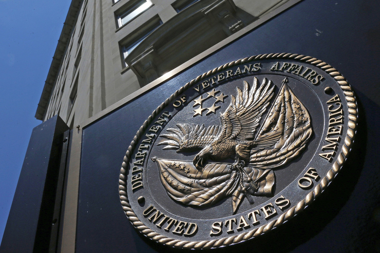 "FILE – This June 21, 2013, file photo, shows the seal affixed to the front of the Department of Veterans Affairs building in Washington.  In a federal lawsuit filed this week, U.S. Navy veteran from South Carolina says he ended up with ""full-blown AIDS,"" because government health care workers never informed him of his positive test result in 1995. He says the test was done as part of standard lab tests at a U.S. Department of Veterans Affairs medical center in Columbia, South Carolina. A V.A. spokeswoman says the agency typically does not comment on pending litigation. (AP Photo/Charles Dharapak, File)"