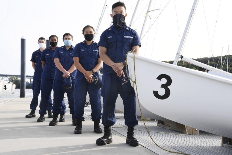In this Monday Sept. 14, 2020 photo, From back left, Coast Guard Academy Cadets Henry Smith, Branyelle Carillo, Mia Haskovec, Jordan Park, and Tyler Huynh, pose for a photograph at the Seamanship Sailing Center at the United State Coast Guard Academy in New London, Conn. A group of Coast Guard cadets spent part of their summer filling in on a critical national security mission after a case of COVID-19 sidelined crew members on a cutter being sent to patrol the US-Russia border. (AP Photo/Jessica Hill)