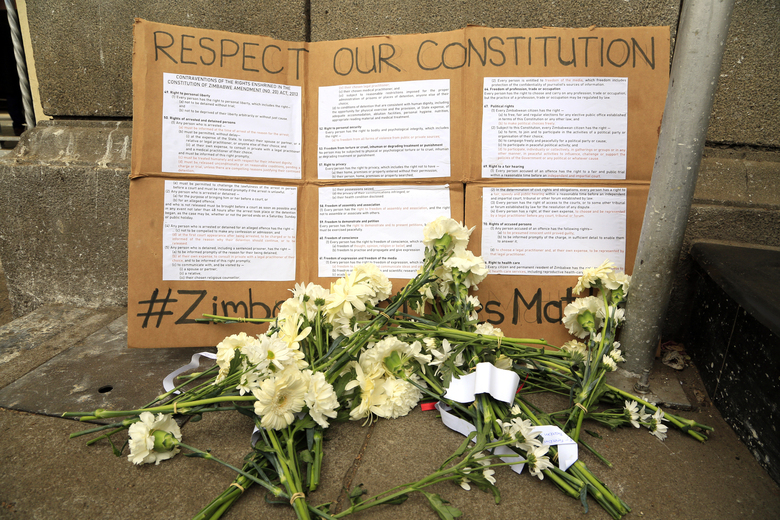 """Flowers are placed outside the High Court during a protests by lawyers outside the High Court while awaiting a bail hearing for jailed journalist Hopwell Chin'ono, in Harare, Wednesday, Sept. 2, 2020. A Zimbabwean court will on Wednesday rule on a fresh bail bid by Chin'ono, in jail for more than a month, at a time his lawyers say prison authorities are forcing him to mingle with other prisoners despite showing symptoms """"consistent"""" with COVID-19.( AP Photo/Tsvangirayi Mukwazhi)"""