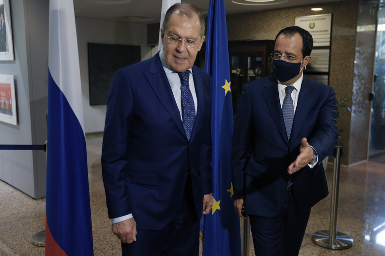 Russian Foreign Minister Sergey Lavrov, left, is greeted by his Cypriot counterpart Nikos Christodoulides as he arrives at the foreign ministry house for a meeting in the capital Nicosia, Cyprus, Tuesday, Sept. 8, 2020. Lavrov is paying an official visit to Cyprus amid heightened tensions over Turkey's search for energy resources in east Mediterranean waters where Greece and Cyprus claim as having exclusive economic rights. (AP Photo/Petros Karadjias)