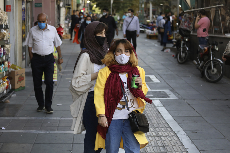 People wearing protective face masks to help prevent the spread of the coronavirus walk on a sidewalk of a commercial street in Tehran, Iran, Sunday, Sept. 20, 2020. Iran's president dismissed U.S. efforts to restore all U.N. sanctions on the country as mounting economic pressure from Washington pushed the local currency down to its lowest level ever on Sunday. (AP Photo/Vahid Salemi)