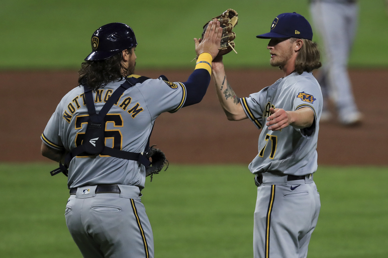 Milwaukee Brewers' Jacob Nottingham, left, high fives Josh Hader, right, in the ninth inning during a baseball game against the Cincinnati Reds in Cincinnati, Tuesday, Sept. 22, 2020. (AP Photo/Aaron Doster)