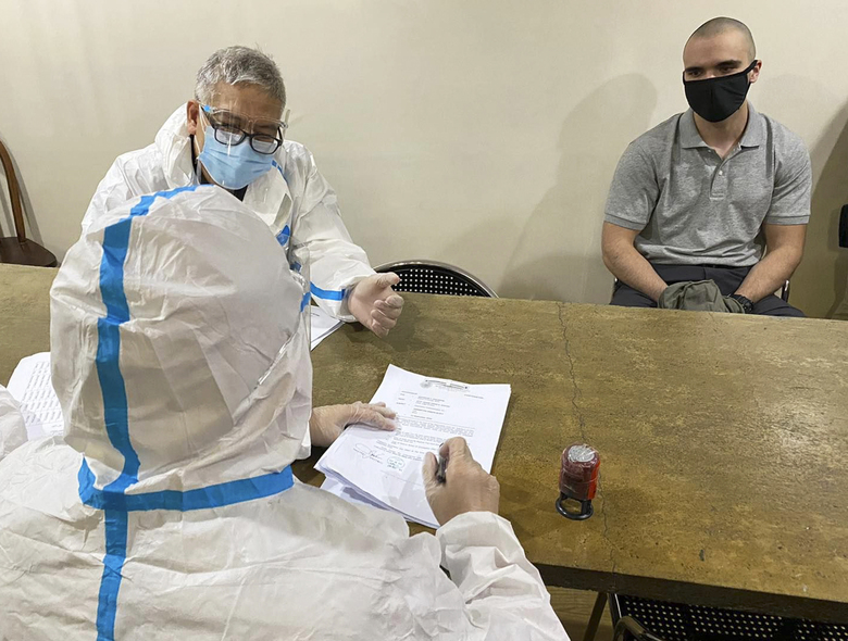 In this photo provided by the Philippines' Bureau of Immigration Public Information Office, (PIO), U.S. Marine Lance Cpl. Joseph Scott Pemberton, right, sits as Bureau of Immigration agents wearing protective suits check his documents before boarding a U.S. military plane at the airport in Manila, Philippines, Sunday, Sept. 13, 2020. Pemberton, a U.S. Marine convicted of killing a Filipino transgender woman, was deported Sunday after a presidential pardon cut short his detention in a case that renewed outrage over a pact governing American military presence in the Philippines. (Bureau of Immigration PIO via AP)
