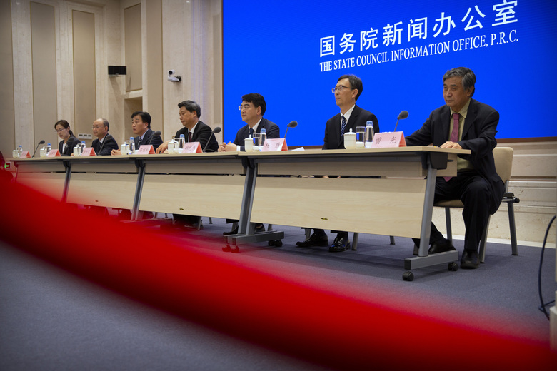 Chinese health officials attend a press conference held to discuss COVID-19 vaccine-related issues at the State Council Information Office in Beijing, Friday, Sept. 25, 2020. A Chinese health official said Friday that the country's annual production capacity for COVID-19 vaccines will top 1-billion next year, following an aggressive government support program for new factories. (AP Photo/Mark Schiefelbein)