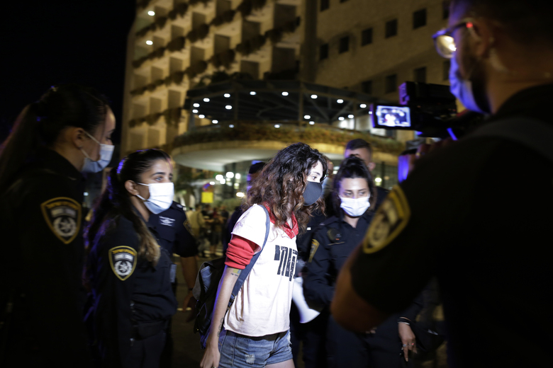 Police lead away a protester as they forcibly clear the square outside of Prime Minister Benjamin Netanyahu's residence in Jerusalem, Saturday, Sept. 26, 2020, during a three-week nationwide lockdown in Israel to curb the spread of the coronavirus. (AP Photo/Maya Alleruzzo)
