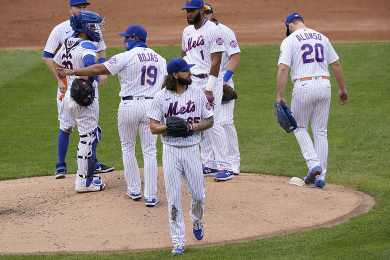 New York Mets starting pitcher Robert Gsellman (65) looks at the scoreboard as he leaves the mound after manager Luis Rojas (19) removed him during the second inning of a makeup baseball game against the New York Yankees at Citi Field, Thursday, Sept. 3, 2020, in New York. (AP Photo/Kathy Willens)