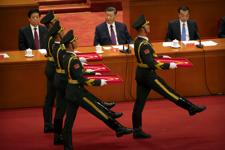 Chinese President Xi Jinping, center, watches as an honor guard carrying medals marches at an event to honor some of those involved in China's fight against COVID-19 at the Great Hall of the People in Beijing, Tuesday, Sept. 8, 2020. Chinese leader Xi Jinping is praising China's role in battling the global coronavirus pandemic and expressing support for the U.N.'s World Health Organization, in a repudiation of U.S. criticism and a bid to rally domestic support for Communist Party leadership. (AP Photo/Mark Schiefelbein)