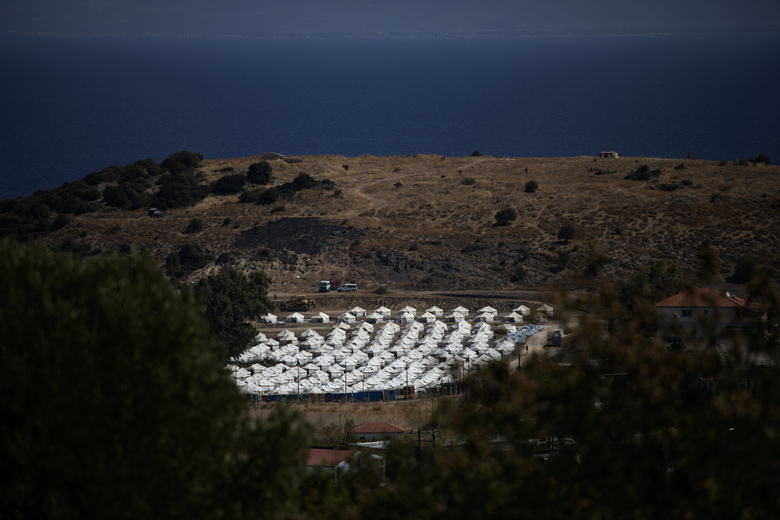 A general view of the temporary camp for refugees and migrants near Mytilene town, on the northeastern island of Lesbos, Greece, Sunday Sept. 13, 2020. Greek authorities have been scrambling to find a way to house more than 12,000 people left in need of emergency shelter on the island after the fires deliberately set on Tuesday and Wednesday night gutted the Moria refugee camp.(AP Photo/Petros Giannakouris)