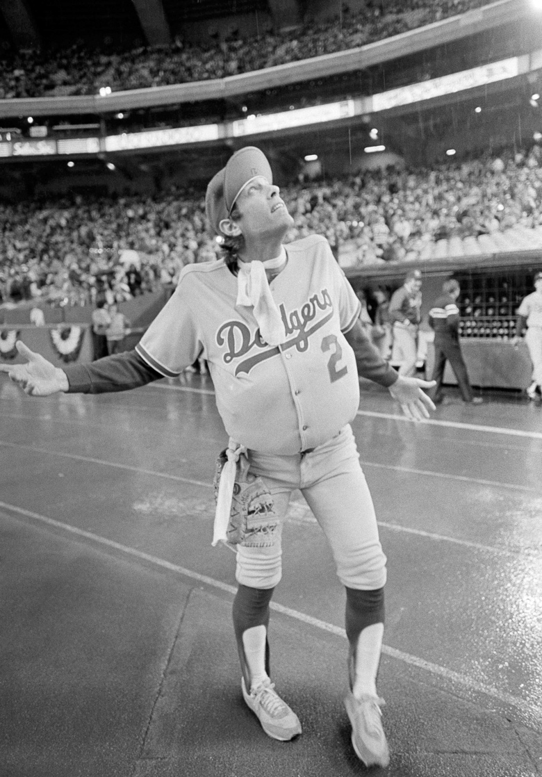 FILE – In this Oct. 18, 1981, file photo, Los Angeles Dodgers outfielder Jay Johnstone, wearing a padded version of manager Tommy Lasorda's uniform, checks the progress of a rain delay before a National League Playoff baseball game with the Expos in Montreal. Johnstone, who won World Series championships as a versatile outfielder with the New York Yankees and Los Angeles Dodgers while being baseball's merry prankster, died Saturday, Sept. 26, of complications from COVID-19 at a nursing home in Granada Hills, Calif., his daughter Mary Jayne Sarah Johnstone said Monday, Sept. 28, 2020. He was 74.  He also from dementia in recent years, his daughter said. (AP Photo/Barrett, File)