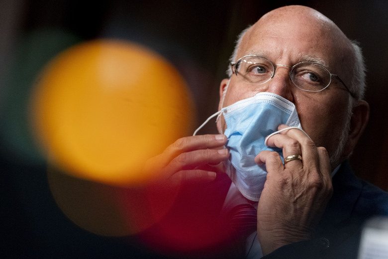 CDC Director Dr. Robert Redfield puts his mask back on after speaking at a Senate Appropriations subcommittee hearing on Wednesday. (AP Photo/Andrew Harnik, Pool, File)
