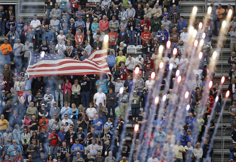 FILE – Fans cheer and wave a flag as fireworks explode during the playing of the national anthem before the start the Xfinity series auto race at Daytona International Speedway, Saturday, Feb. 21, 2015, in Daytona Beach, Fla. NASCAR has built itself around its traveling show, every weekend a super-charged event of concerts, camping and infield carousing that closes with a Cup race. The party has been canceled during the pandemic but the playoffs go on, starting Sunday, Sept. 6, 2020, without any of the pomp and circumstance. (AP Photo/John Raoux, File)