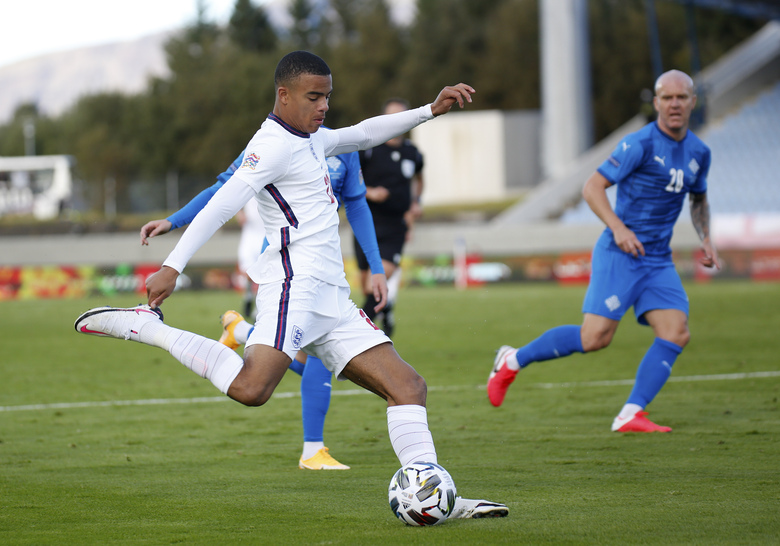 England's Mason Greenwood takes a shot during the UEFA Nations League soccer match between Iceland and England in Reykjavik, Iceland, Saturday, Sept. 5, 2020. England players Phil Foden and Mason Greenwood have been dropped for Tuesday's game against Denmark after breaching coronavirus rules in Iceland. They will return to England from Reykjavik rather than traveling to Copenhagen on Monday Sept. 7, 2020, after social media video was published in Iceland purporting to show the players meeting women from outside the team bubble. (AP Photo/Brynjar Gunnarson)