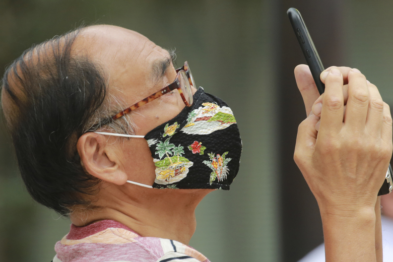 A man wearing face masks to protect against the spread of the new coronavirus takes a pictures in Tokyo, 2020. (AP Photo/Koji Sasahara)