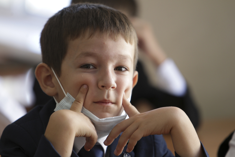 """A boy wearing a face mask to protect against coronavirus sits in a classroom during a ceremony marking the start of classes at a school as part of the traditional opening of the school year known as """"Day of Knowledge"""" in Grozny, Russia, Tuesday, Sept. 1, 2020. Across the country, schools start their usually festive opening day on Sept. 1. (AP Photo/Musa Sadulayev)"""
