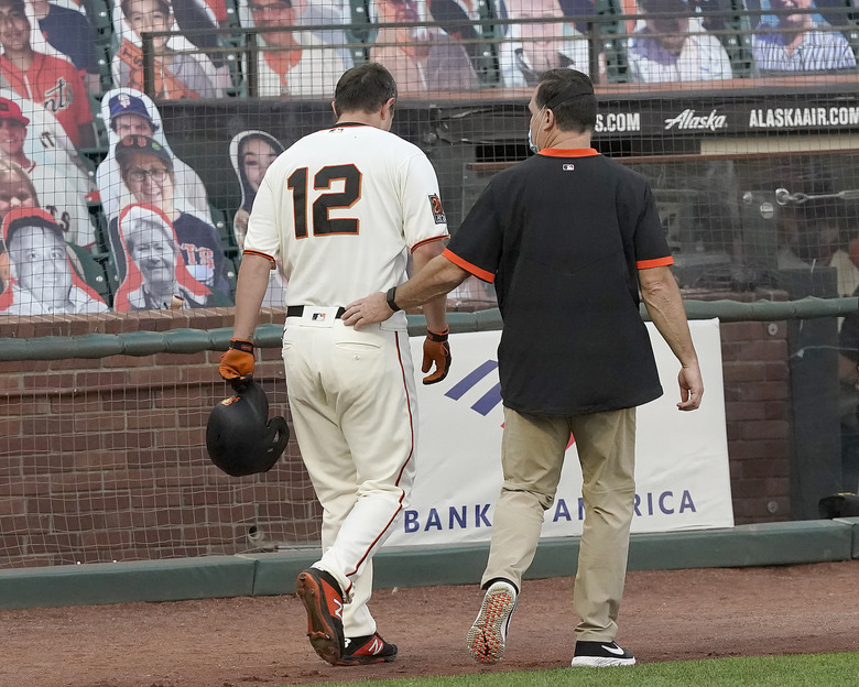 San Francisco Giants' Alex Dickerson (12) walks off the field with the team trainer after getting hit by a ball that bounced off his bat during the fifth inning against of a baseball game against the Arizona Diamondbacks, Monday, Sept. 7, 2020, in San Francisco. (AP Photo/Tony Avelar)