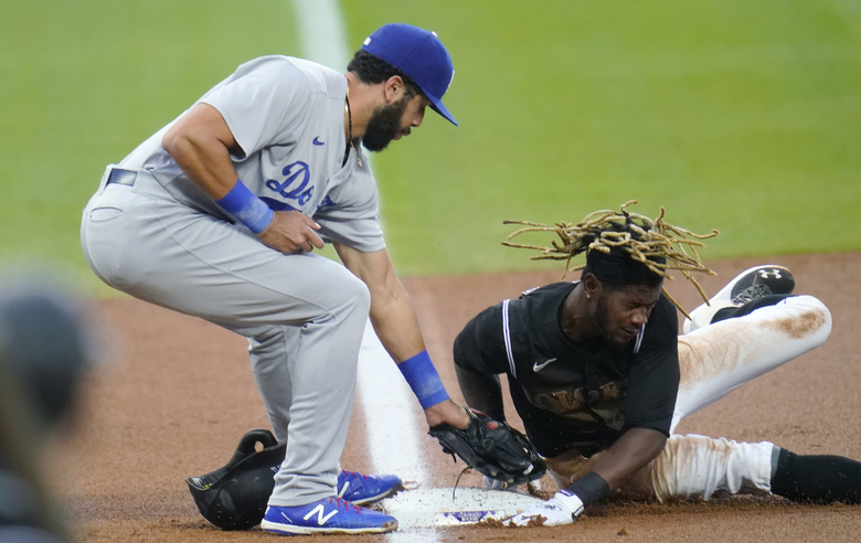 Los Angeles Dodgers third baseman Edwin Rios, left, applies a late tag as Colorado Rockies' Raimel Tapia steals third base during the first inning of a baseball game Saturday, Sept. 19, 2020, in Denver. (AP Photo/David Zalubowski)