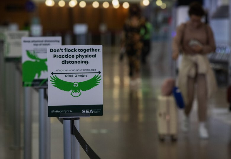 Signs at Sea-Tac Airport remind visitors of social distancing, hand washing and mask-wearing guidelines. (Ellen M. Banner / The Seattle Times)