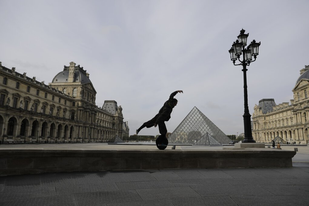 Aurelien Nizet, 26, keeps his balance on his hoverboard in the almost empty courtyard of the Louvre museum, on Wednesday. French President Emmanuel Macron is giving a nationally televised interview Wednesday night to speak about the virus. French media reports say Macron will step up efforts on social media to press the need for virus protections among young people. (Lewis Joly / The Associated Press)