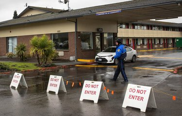 A security guard walks in front of the EconoLodge in Kent where people are being quarantined for the coronavirus.  A person who was in quarantine at this location left early Friday morning, March 13, 2020, stole some items from the 7-11 across the street and boarded a bus.   It is not known if he is infected with the virus or not.    213338