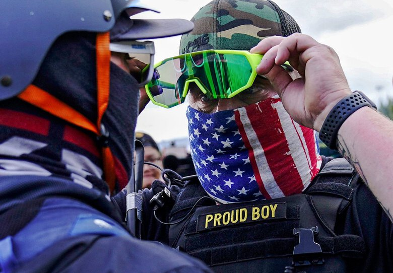 A member of the Proud Boys stands in front of a counter protester as other right-wing demonstrators rallied on Sept. 26 in Portland. (John Locher / AP, file)