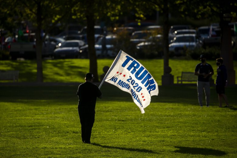 A supporter of President Donald Trump leaves a rally in Bellevue's Downtown Park on Saturday.  (Bettina Hansen / The Seattle Times)