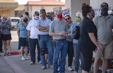 Voters wait in line outside of an Ace Hardware store in Odessa, Texas, for the first day of early voting in Texas on Tuesday, Oct. 13, 2020. In Texas, the last day to apply for ballot by mail has to be received by Oct. 23, and the last day of early voting is Oct. 30. (Eli Hartman/Odessa American via AP) TXODE103 TXODE103