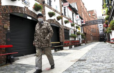 A man wearing a face mask walks past a closed pub in Belfast, Northern Ireland, Friday, Oct. 16, 2020. Northern Ireland has brought in restrictions to try and 'circuit break' the growing number of COVID-19 infections, they include -pubs closing from 1800, Friday, along with funerals and weddings limited to 25 people from for a period of 4 weeks. (AP Photo/Peter Morrison) XPM101 XPM101