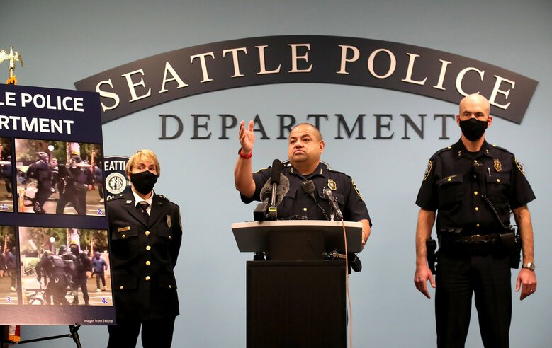 Seattle's interim police Chief Adrian Diaz, center, conducts a news conference Monday. Diaz and Mayor Jenny Durkan have said the city must start hiring officers again in 2021 to maintain 911 response times and comply with court-ordered police reforms. (Greg Gilbert / The Seattle Times)