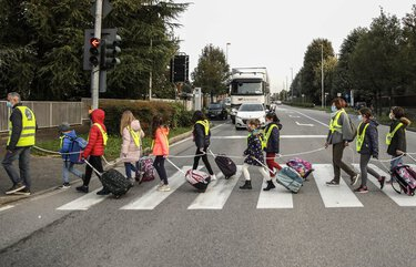 Children, escorted by volunteers, walk to school holding on to a rope to help maintain social distancing and curb the spread of COVID-19, in Bellusco, northern Italy, Tuesday, Oct. 20, 2020. (AP Photo/Luca Bruno) XLB101 XLB101