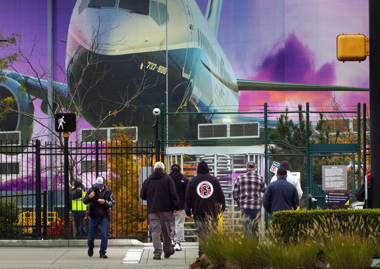 Boeing workers head into the manufacturing plant where 737's are built in Renton Wednesday, October 28, 2020.  Boeing said Wednesday that by the end of next year it will employ 31,000 fewer people company-wide than at the beginning of this year.  (Ellen M. Banner / The Seattle Times)