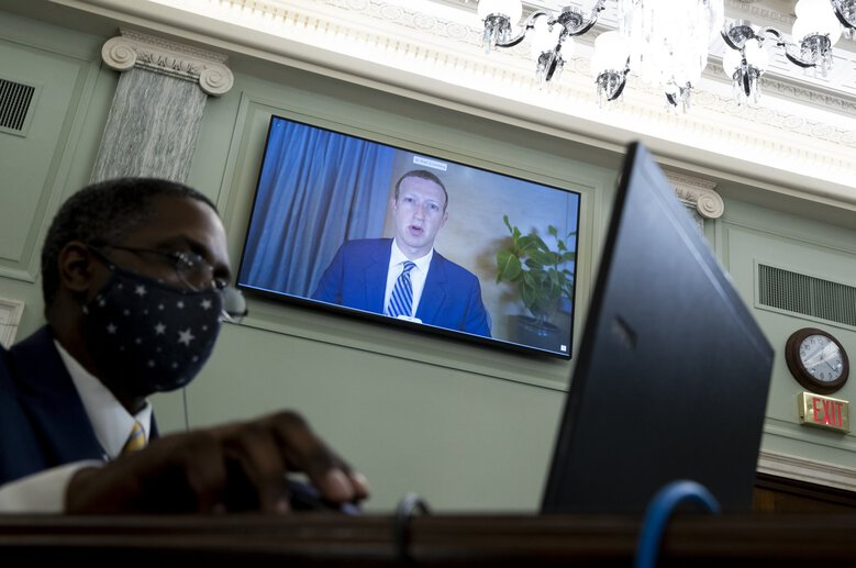 Facebook CEO Mark  Zuckerberg appears on a screen as he speaks remotely during a hearing before the Senate Commerce Committee on Capitol Hill om Wednesday. The committee summoned the CEOs of Twitter, Facebook and Google to testify. (Michael Reynolds/Pool via AP)