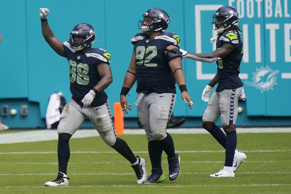 Seattle Seahawks defensive end Alton Robinson (98) celebrates after his tackle against Miami Dolphins running back Myles Gaskin (37) forced a field goal, during the second half of an NFL football game, Sunday, Oct. 4, 2020, in Miami Gardens, Fla. (Lynne Sladky / The Associated Press)