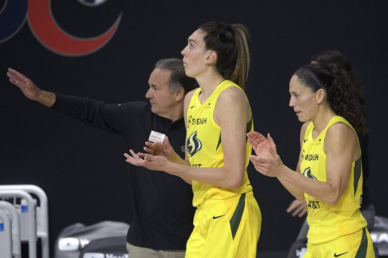 Seattle Storm forward Breanna Stewart, front left, and guard Sue Bird, right, applaud as head coach Gary Kloppenburg, back left, reacts after winning Game 2 of basketball's WNBA Finals over the Las Vegas Aces, Sunday, Oct. 4, 2020, in Bradenton, Fla.  (Phelan M. Ebenhack / The Associated Press)