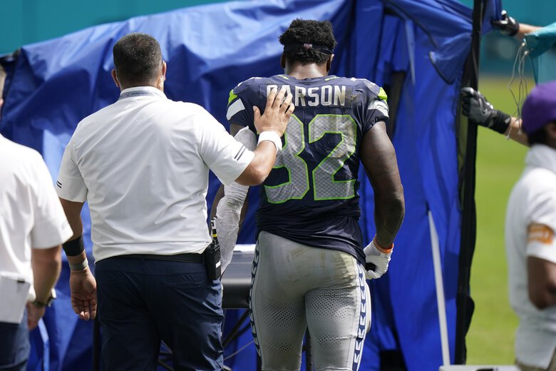 Seattle Seahawks running back Chris Carson (32) is taken off the field, during the first half of an NFL football game against the Miami Dolphins, Sunday, Oct. 4, 2020 in Miami Gardens, Fla. (Wilfredo Lee / AP)