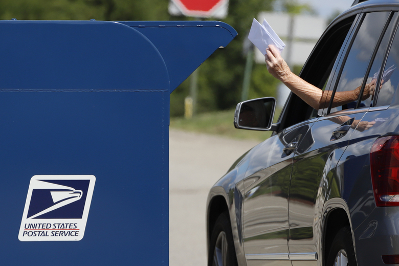 FILE – In this Aug. 19, 2020, file photo, a person deposits mail in a box outside United States Post Office in Cranberry Township, Pa. U.S. Postal Service records show delivery delays have persisted across the country as millions of Americans began voting by mail, raising the possibility of ballots being rejected because they arrive too late. Parts of the politically coveted battleground states of Wisconsin, Michigan, Pennsylvania and Ohio fell short of delivery goals by wide margins as the agency struggles to regain its footing after a tumultuous summer. (AP Photo/Gene J. Puskar, File)
