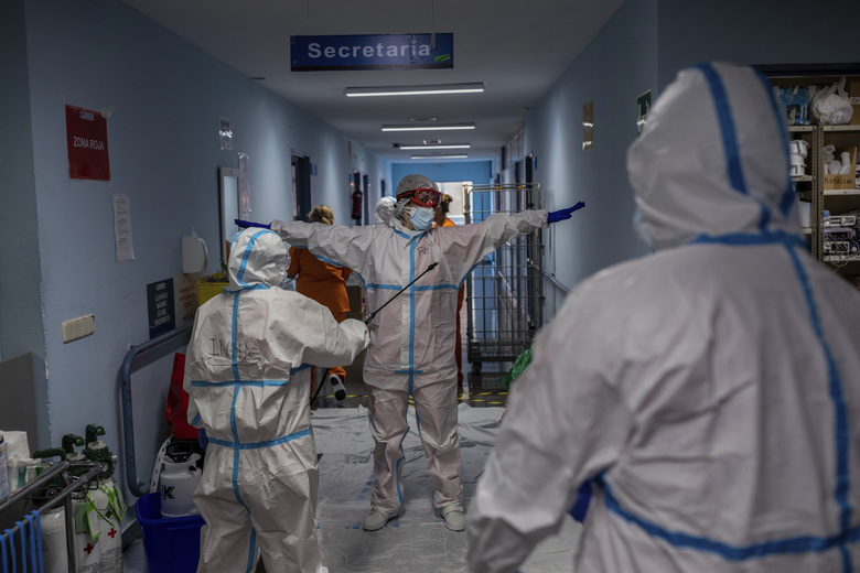 A medical team member is disinfected before leaving the COVID-19 ward at the Severo Ochoa hospital in Leganes, outskirts of Madrid, Spain, Friday, Oct. 9, 2020. At the peak of the first wave, ICU wards were given over to haste, desperation and even cluelessness about what to do. Now, a well-oiled machinery saves some lives and loses others to coronavirus, but without the doomsday atmosphere of March and April. (AP Photo/Bernat Armangue)