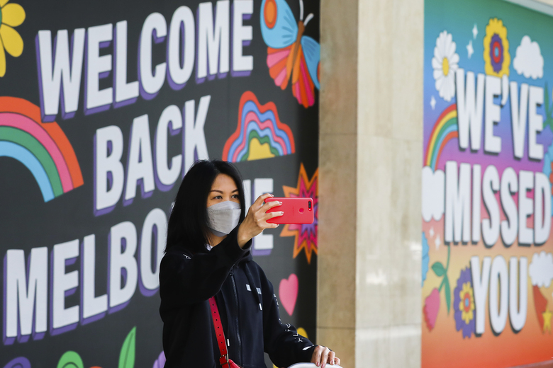 A woman takes a selfie in front of signage in Melbourne, Australia, Wednesday, Oct. 28, 2020. Australia's second largest city of Melbourne which was a coronavirus hotspot emerges from a nearly four-months lockdown, with restaurants, cafes and bars opening and outdoor contact sports resuming on Wednesday. (AP Photo/Asanka Brendon Ratnayake)