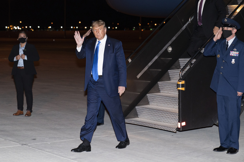 President Donald Trump waves as he steps off Air Force One at Las Vegas McCarran International Airport, Sunday, Oct. 18, 2020, in Las Vegas. (AP Photo/Alex Brandon)
