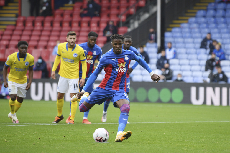 Crystal Palace's Wilfried Zaha scores scores his side's opening goal with a penalty kick during an English Premier League soccer match between Crystal Palace and Brighton at the Selhurst Park stadium in London, England, Sunday Oct. 18, 2020. (Mike Hewitt/Pool via AP)