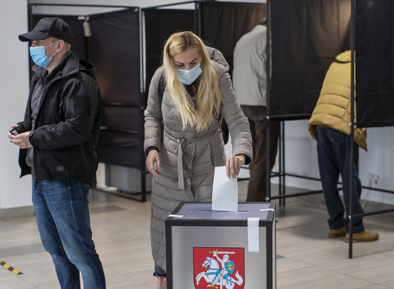 A woman, wearing face masks to protect against coronavirus, casts her ballot at a polling station during the second round of a parliamentary election in Vilnius, Lithuania, Sunday, Oct. 25, 2020. Polls opened Sunday for the run-off of national election in Lithuania, where the vote is expected to bring about a change of government following the first round, held on Oct. 11, which gave the three opposition, center-right parties a combined lead. (AP Photo/Mindaugas Kulbis)
